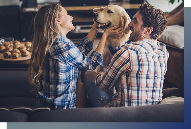 Couple at home playing with dog